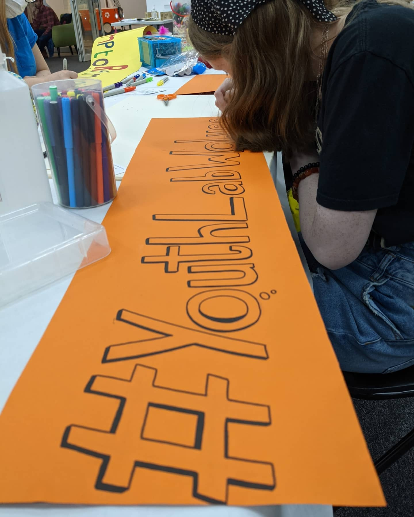 Photograph of a banner, drawn in pen by Curiosity staff member Chloe, who is hunched over.