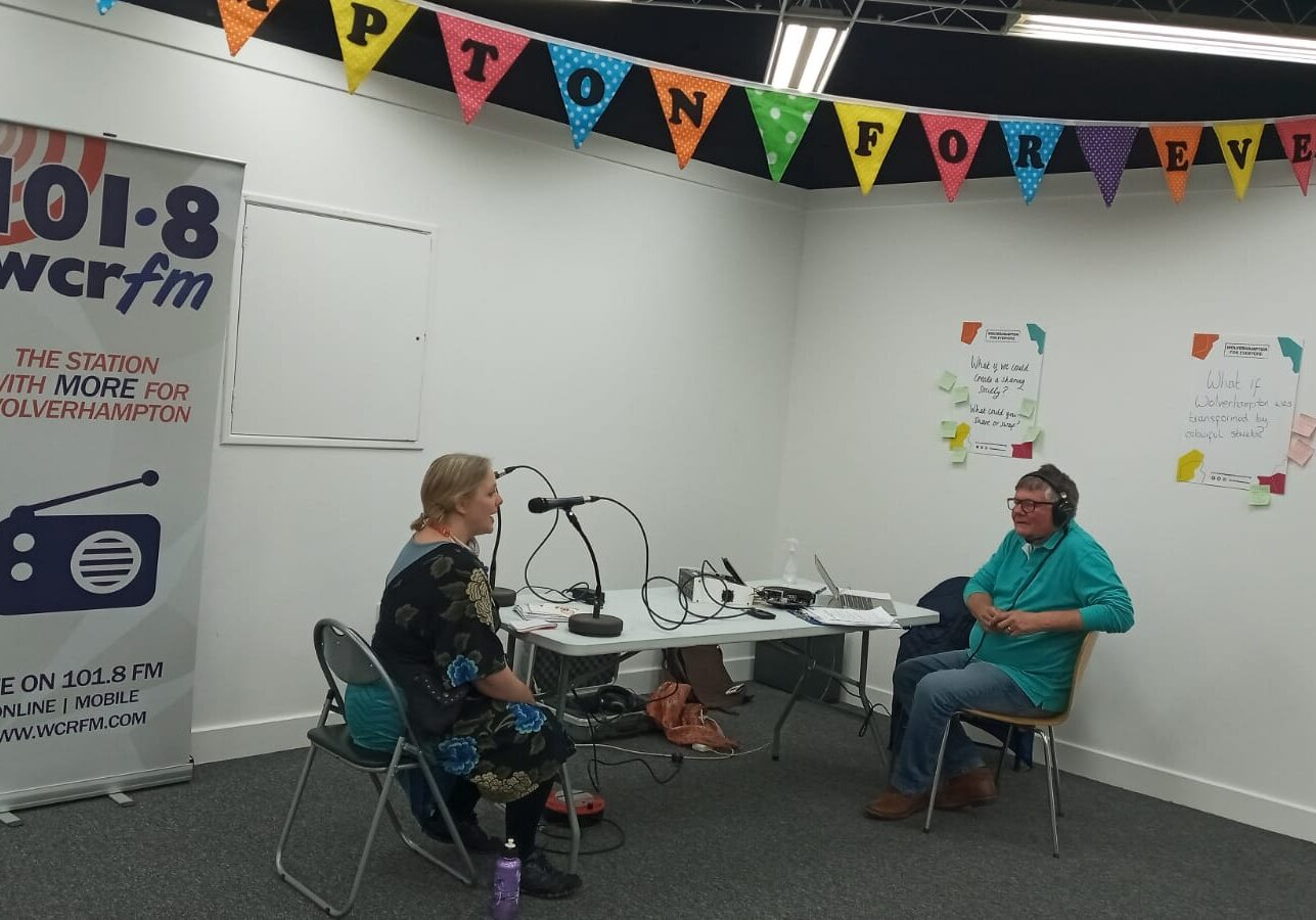 Photograph of Creative Director Jenny Smith being interviewed at a table in the corner of the room. To the left is a radio banner, reading WCR radio.